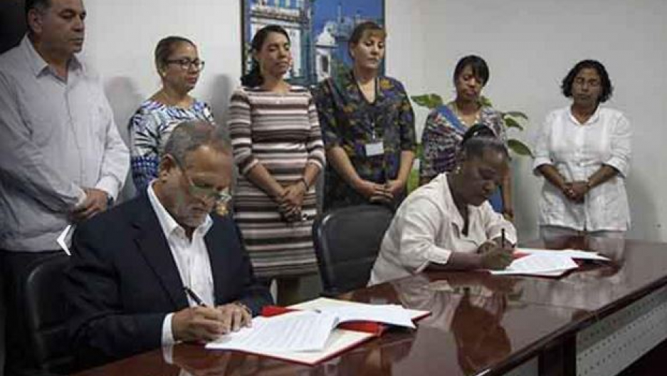 Scott Gilbert (L) signs a business deal with Cuba representatives to buy 80 tons of artisanal marabu charcoal.