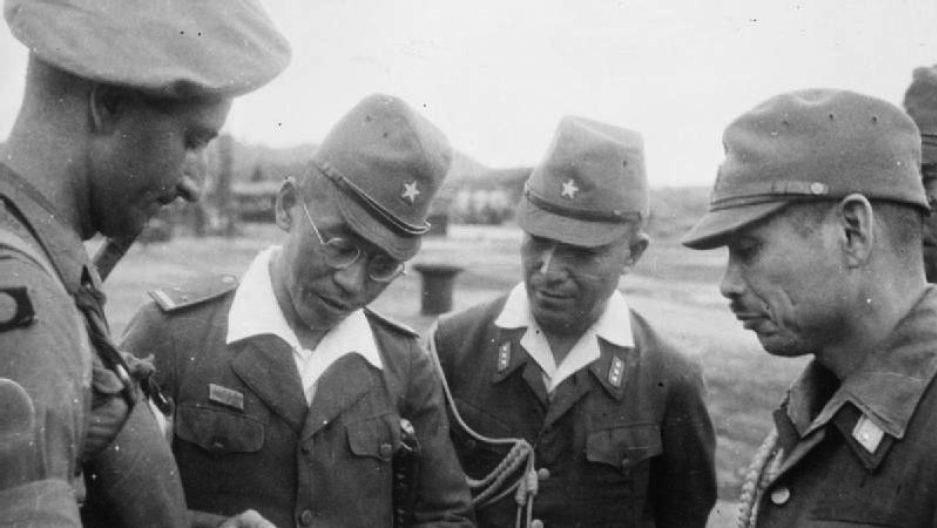 Japanese Army officers confer with a British Army officer after the Japanese surrender of Singapore, 1945.