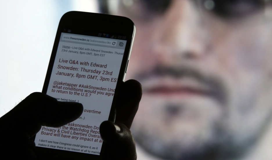 A man uses his phone to read updates about former American NSA contractor Edward Snowden answering users' questions on Twitter.