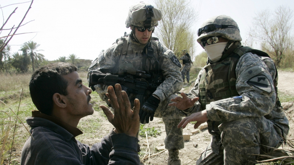 A US soldier of the 2nd Platoon Charlie Troop, 3rd Squadron of 61st Cavalry Regiment questions a man with an interpreter (R) while on patrol with Iraqi National Police in a suburb of Baghdad, March 7, 2007.