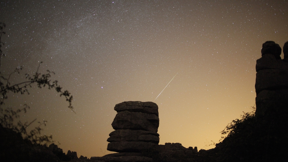 A meteor streaks past stars in the night sky over El Torcal nature park