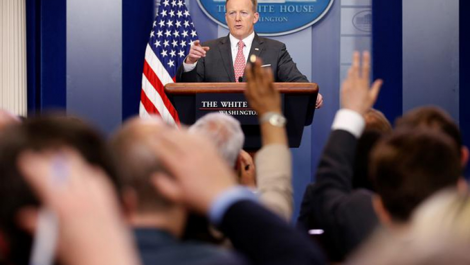 White House Press Secretary Sean Spicer points to a reporter during a press conference as several hands rise up from the crowd of questioning journalists.