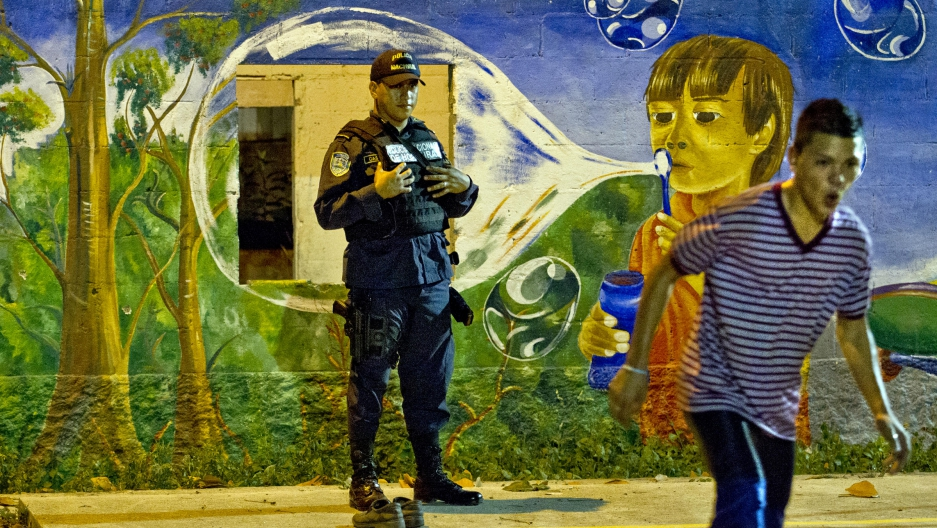 Honduran police officer Marvin Castro patrols this once very dangerous neighborhood of Chamelecón in San Pedro Sula, Honduras.