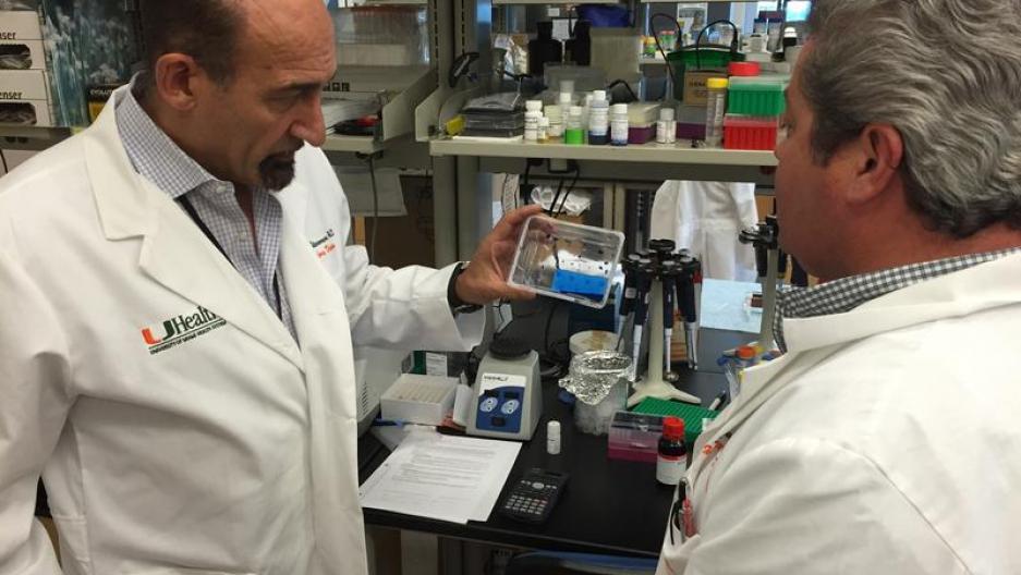 UM's Mario Stevenson (left) examines a new Zika virus detection test at his team's Miami lab.
