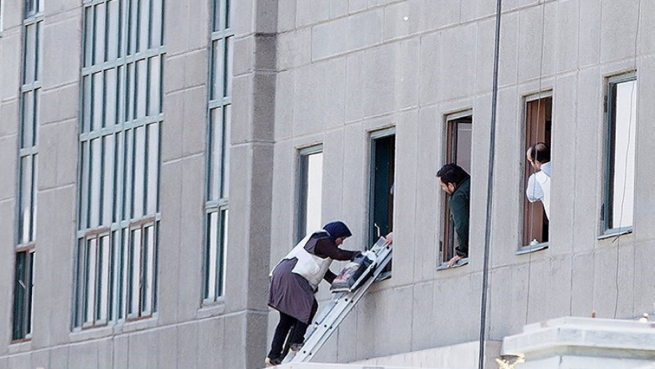 A woman is evacuated during an attack on the Iranian parliament in central Tehran, Iran.