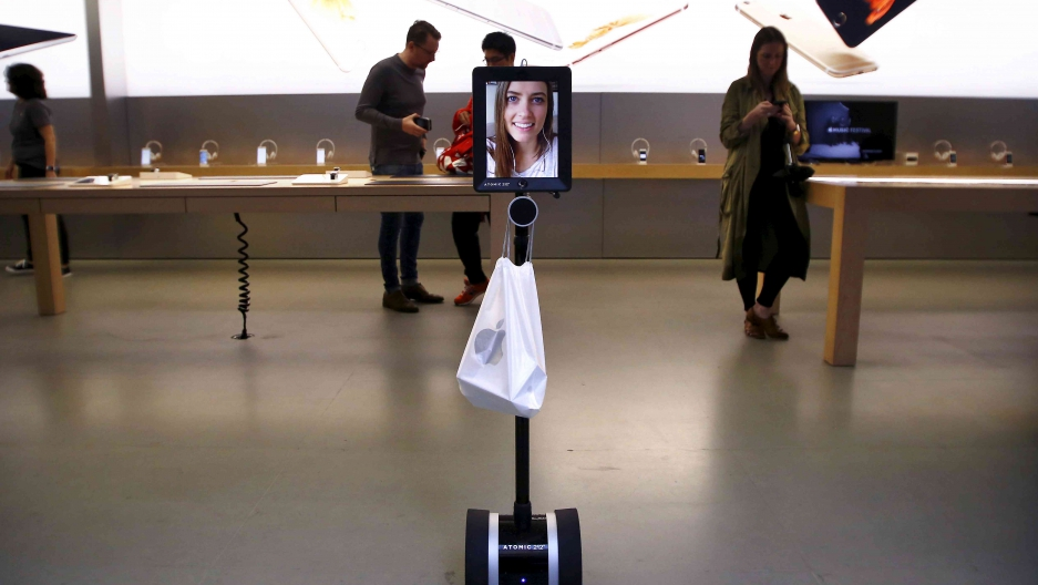 Lucy Kelly is seen on a screen attached to a telepresence robot