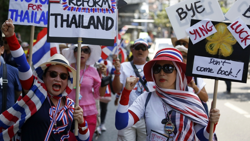 Anti-government protesters carry signs against ousted Prime Minister Yingluck Shinawatra as they march in central Bangkok May 8, 2014. Thailand's anti-corruption agency may decide on Thursday whether to pursue charges against Yingluck that could see her b
