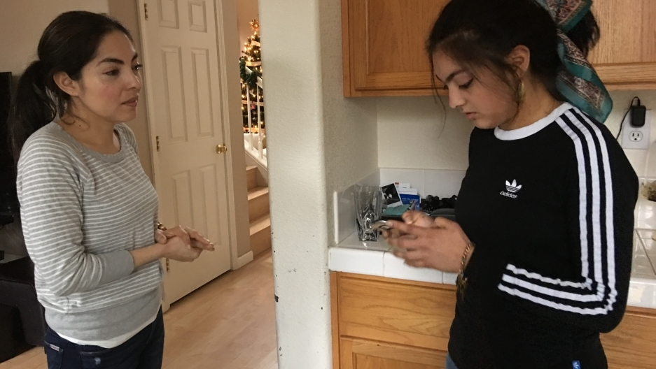 Two woman stand in kitchen, one older and one younger looking at her phone