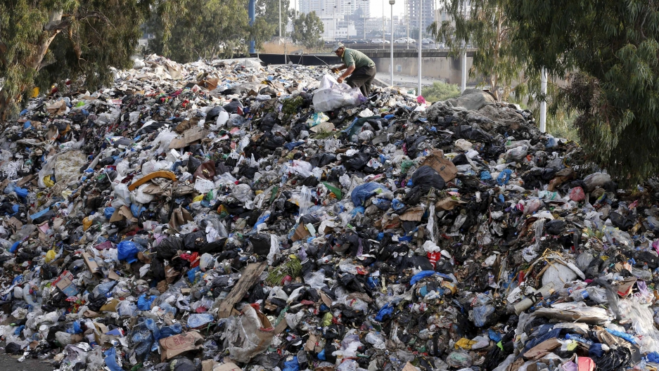 A scavenger sifts through garbage piled on the banks of a Beirut river.