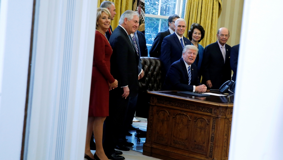 donald trump as seen through the double doors of the oval office surrounded by his advisers