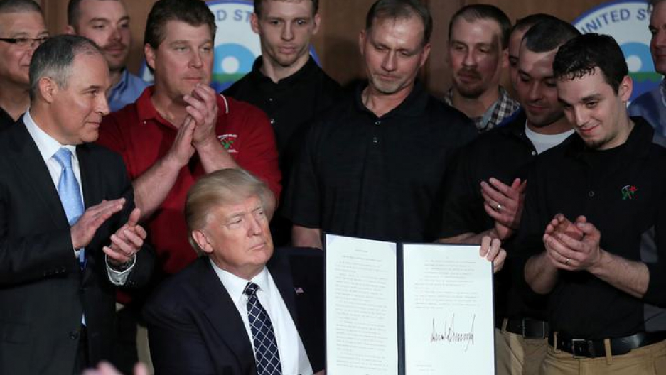"A group of miners wearing black polos and several onlookers watch President Donald Trump as he holds up a signed version of his most recent executive order, ""Promoting Energy Independence and Economic Growth."""