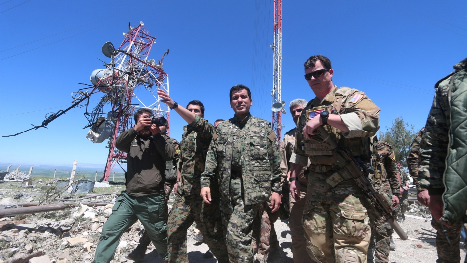 A US military commander, right, walks with a commander from the Kurdish People's Protection Units