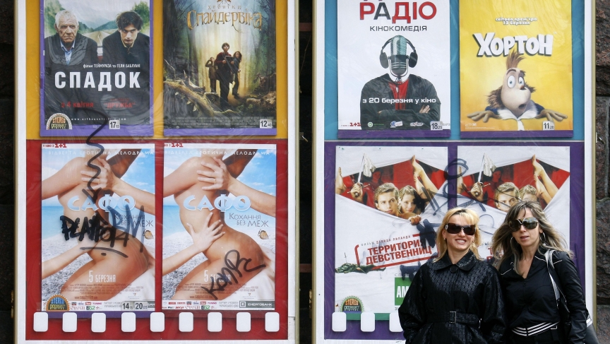 Women walk past a movie theater in central Kiev. Cinemas are the new testing ground in the debate over how to promote the Ukrainian language in the country of 46 million after centuries of dominance from Moscow.