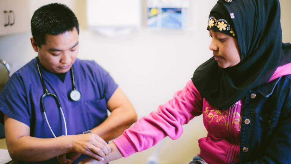 A woman gets her pulse checked at Jericho Road Community Health Center, a health center that focuses on culturally sensitive health care for refugees.