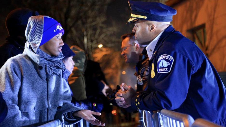 Mohamed Samatar talks to a Minneapolis police officer over a barrier.