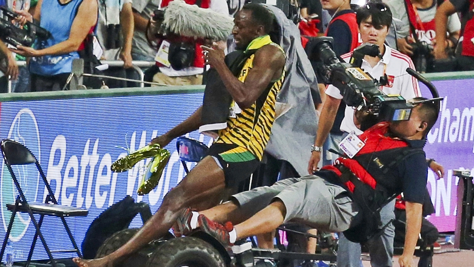 Usain Bolt is hit by a cameraman on a Segway as he celebrates after winning the men's 200 metres final at the 15th IAAF World Championships at the National Stadium in Beijing, China, August 27, 2015.