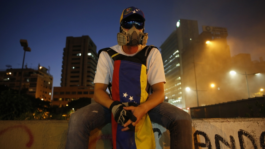 An opposition supporter sits on a wall as protesters block a street at Altamira square in Caracas February 20, 2014.