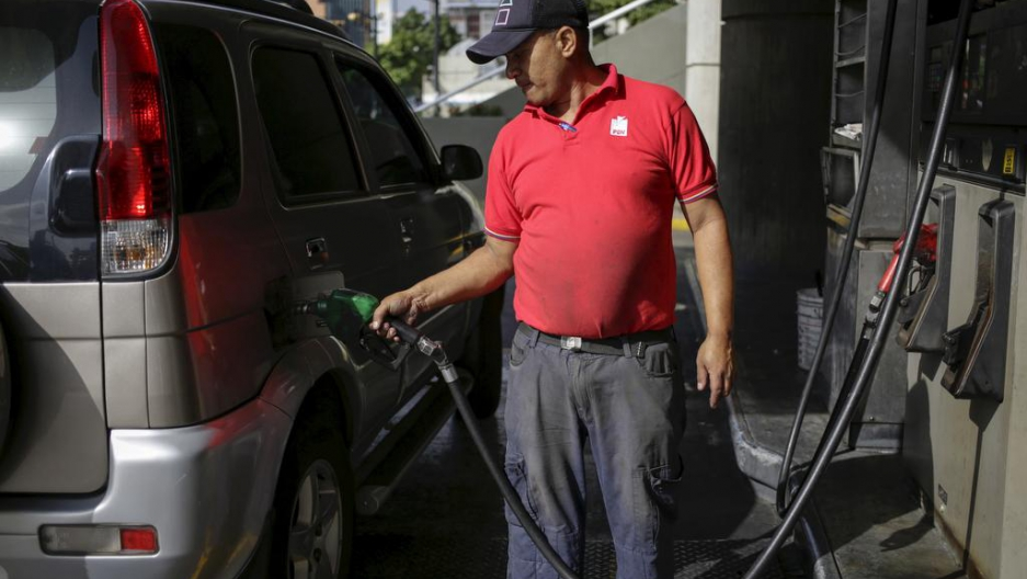 A worker pumps gas into a vehicle at a gas station, which belongs to Venezuela's state oil company PDVSA, in Caracas, on Feb. 12, 2016.