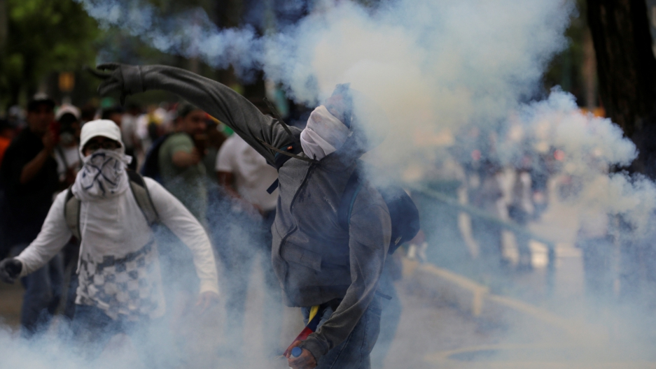 A demonstrator throws a tear gas canister back to police