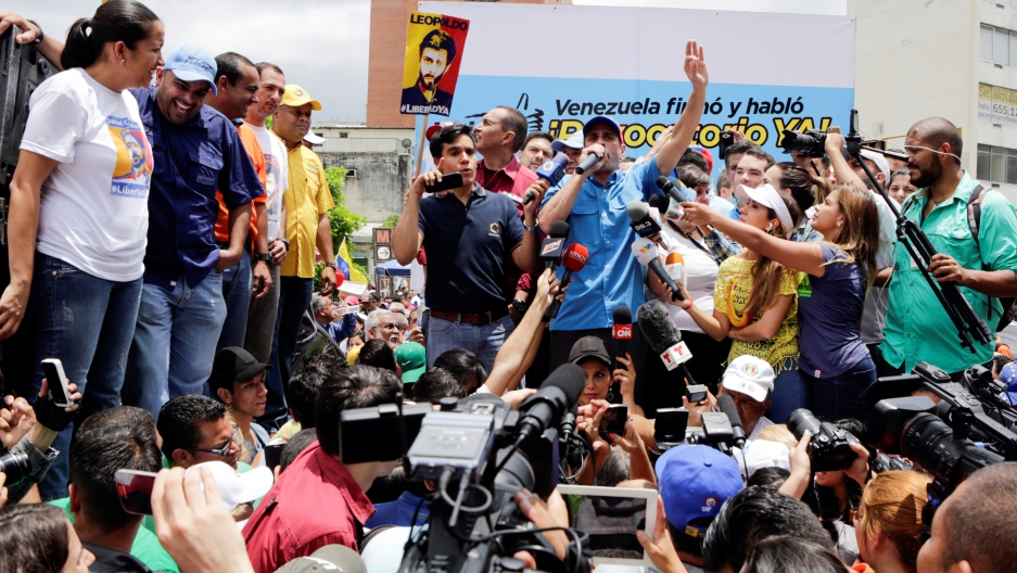 Venezuelan opposition leader and Governor of Miranda state Henrique Capriles (C) speaks during a rally