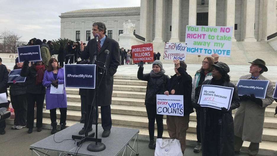 US Senator Sherrod Brown (D-OH) addresses a rally ahead of arguments in a key voting rights case involving a challenge to the Ohio's policy of purging infrequent voters from voter registration rolls outside the US Supreme Court in Washington, Jan. 10, 201