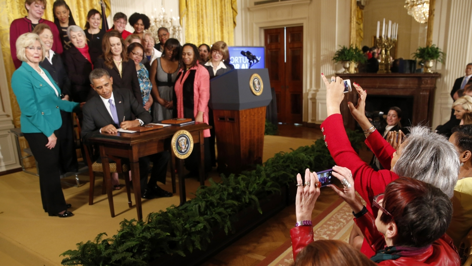 Women legislators take photos as US President Barack Obama signs two new executive actions