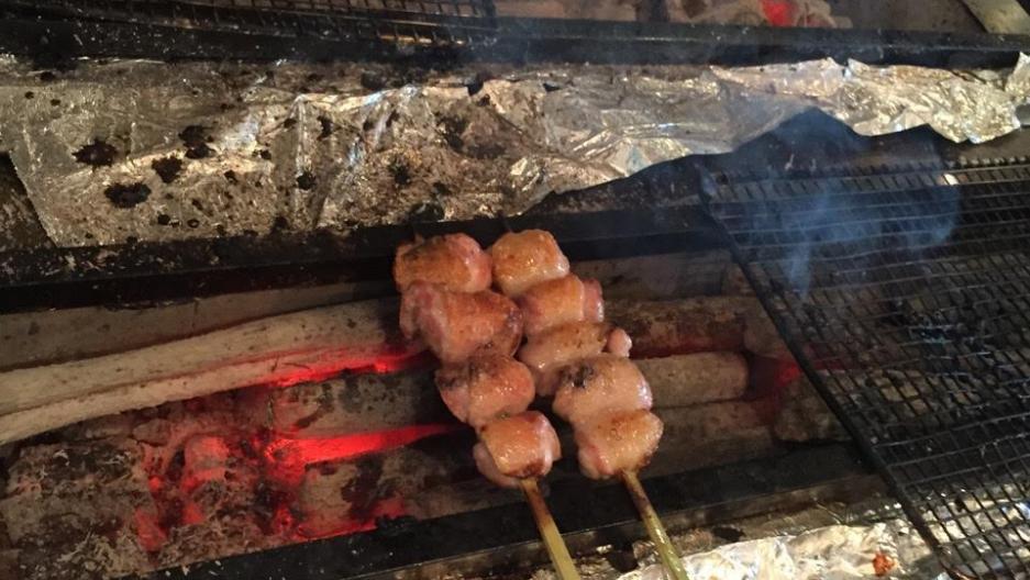 Chicken thighs grilling over binchotan charcoals