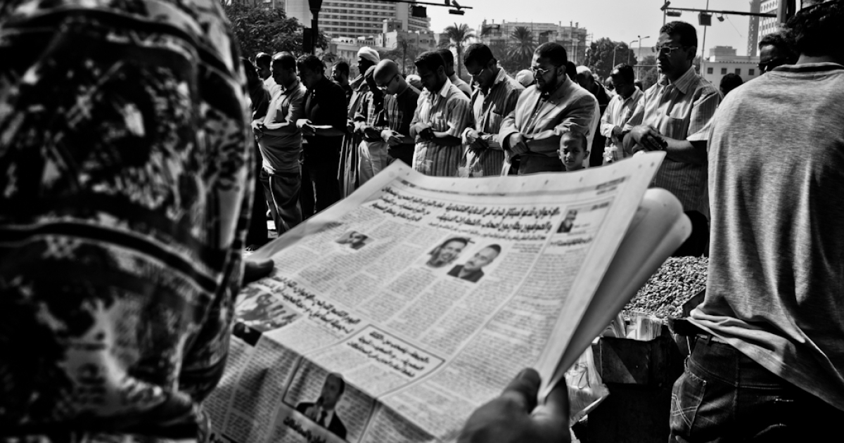 A man reads the newspaper during Friday prayers in Cairo's Tahrir Square.</p>