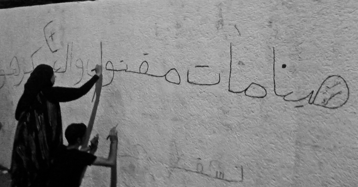 A young woman paints grafitti on a wall next to the Coptic Hospital a day after Maspero clashes between army & protesters killed 27, including young activist Mena Daniel. The grafitti reads,