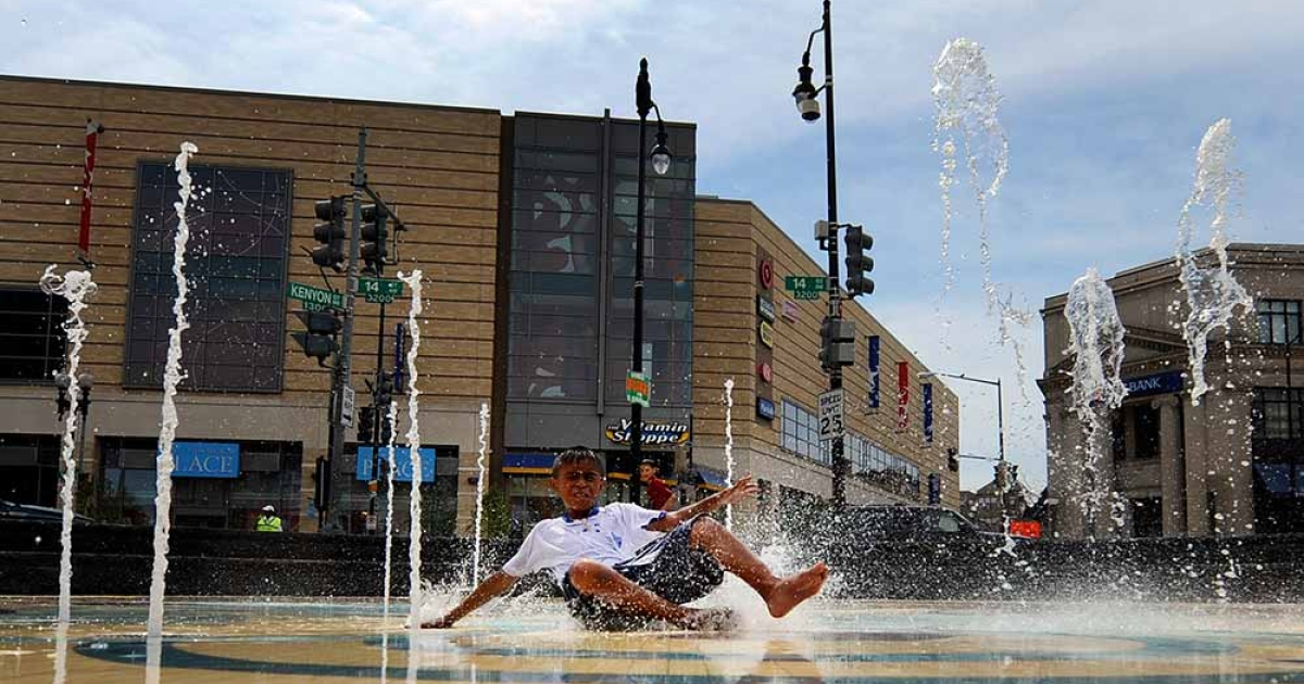 Carlos Mendoza, age 11, slides through a new outdoor interactive water fountain in the Mount Pleasant/Columbia Heights neighborhood of Washington, DC. The area is one of the District's most diverse neighborhoods.</p>