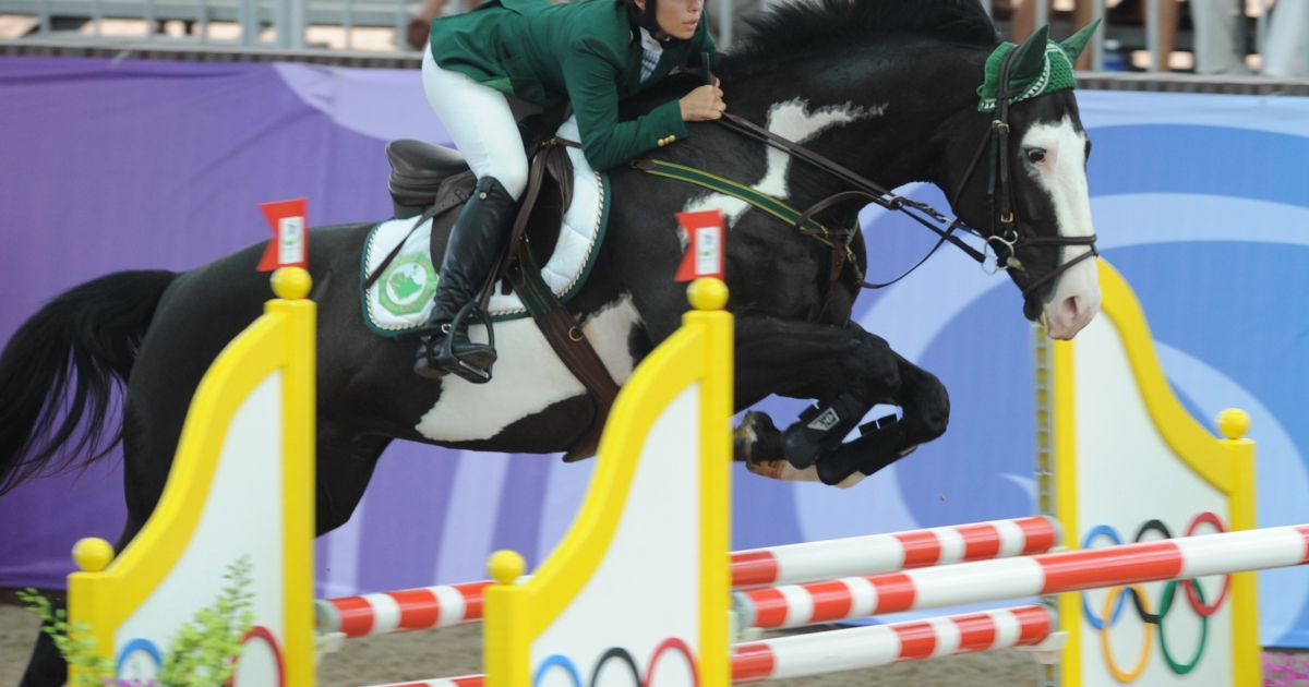 Saudi Dalma Malhas rides her horse named Flash Top Hat into a jump during the equestrian jumping individual round two competition at the Youth Olympic Games 2010 in Singapore on August 22, 2010.</p>