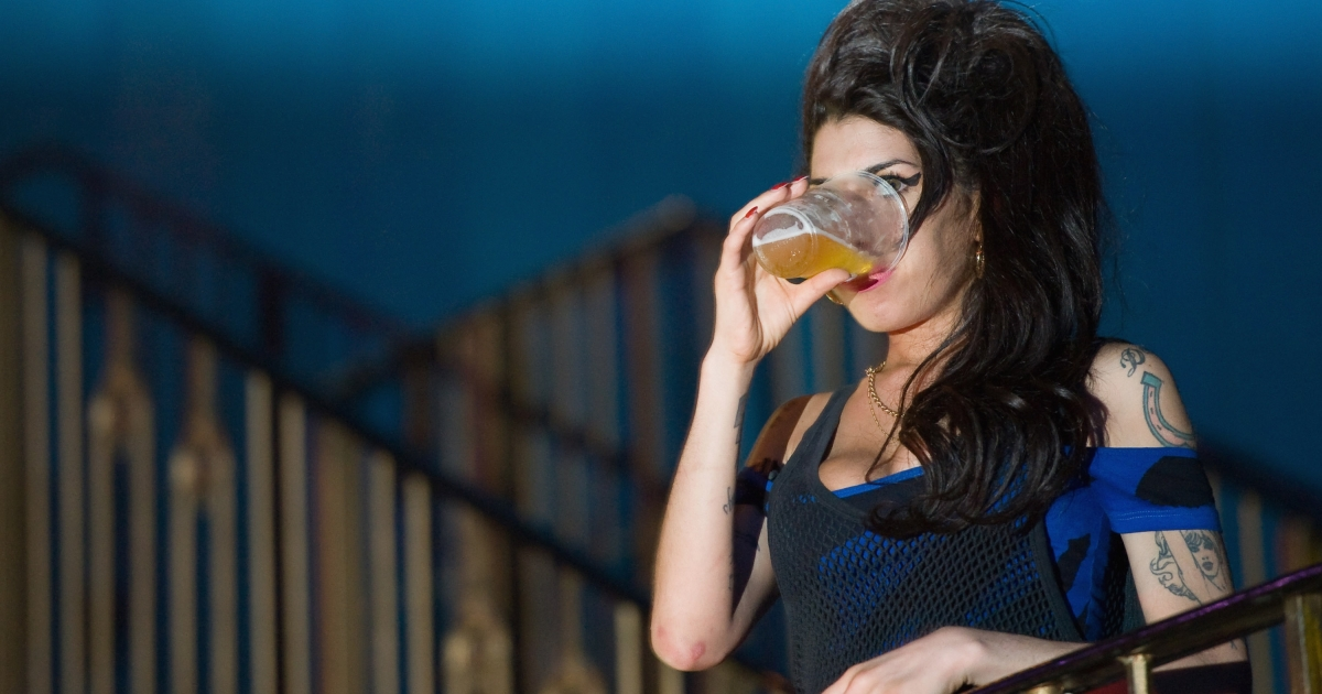 The speed of beer drinking is determined by the shape of the glass says a new study. Above, the late Amy Winehouse enjoys a pint while watching a concert.</p>