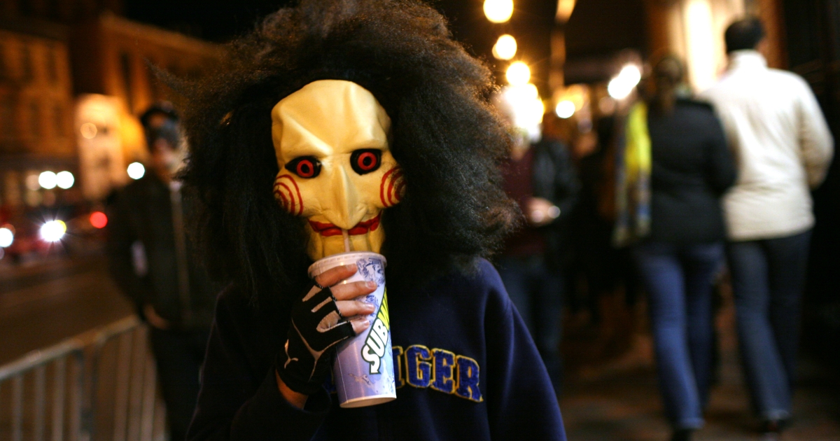 A boy with the Hollywood movie SAW costume drinks subway soda while stroll around the Georgetown neighborhood during Georgetown's annual Halloween party on October 31, 2010 in Washington DC.</p>