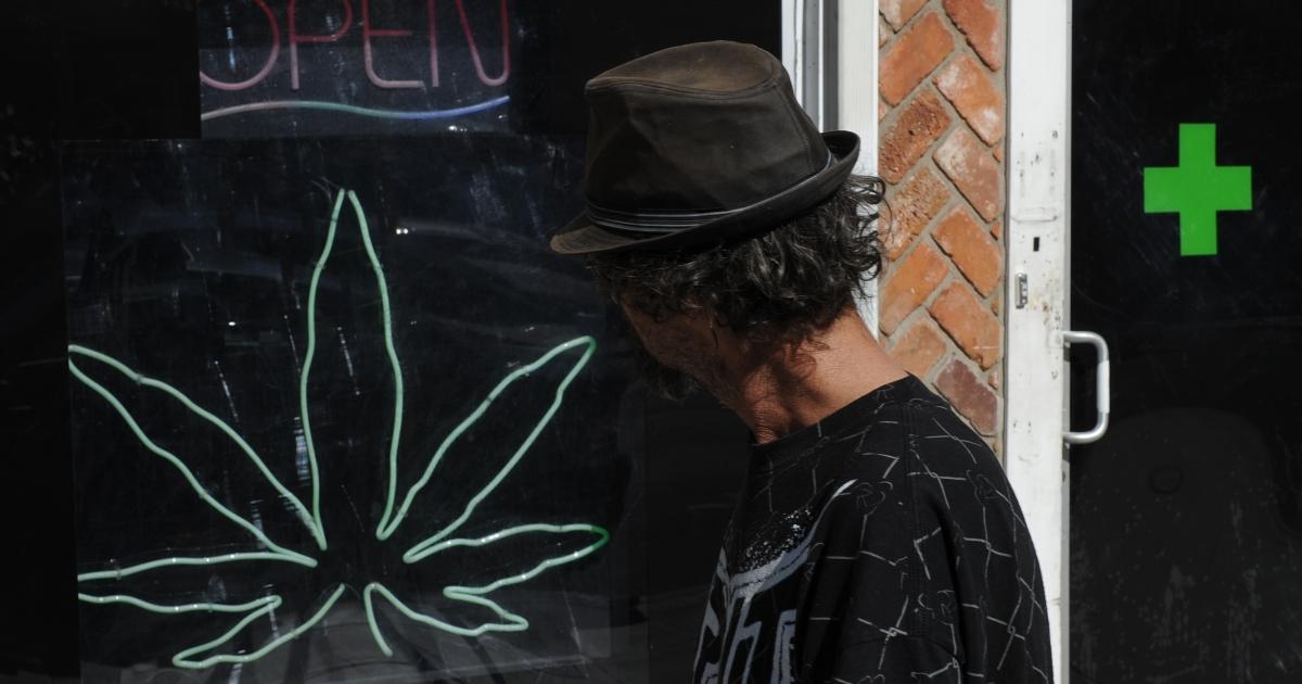 A man walks past a medicinal marijuana dispensary in Los Angeles,CA on November 2, 2010.</p>