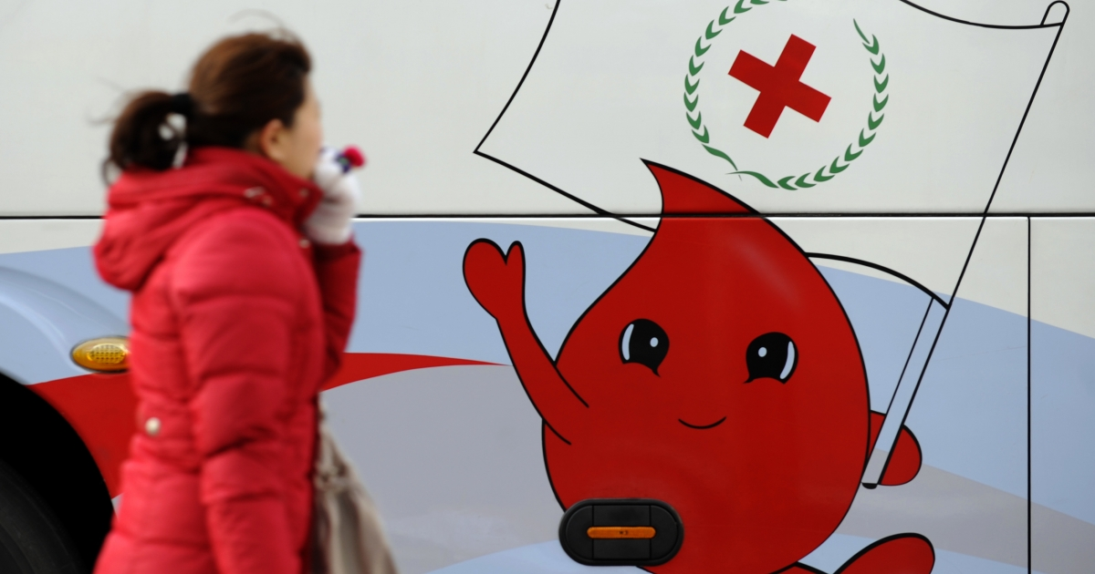 A woman walks past a blood donation sign in downtown Beijing on December 29, 2010.</p>