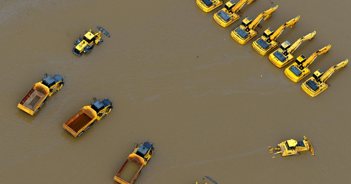 Giant mining trucks and excavators are submerged as flood waters devastate much of Brisbane, the capital of Queensland state, on Jan. 13, 2011. Australia's third-largest city awoke to a