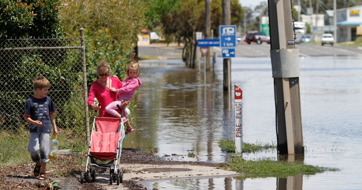 A mother with her children cross flooded road on January 18, 2011 in Horsham, Victoria, Australia.</p>