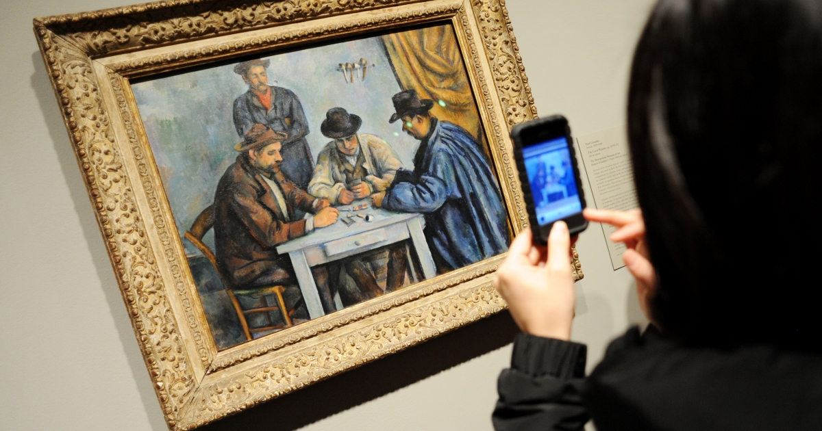 A woman takes a cell phone photograph of Paul Cézanne's 1890-92