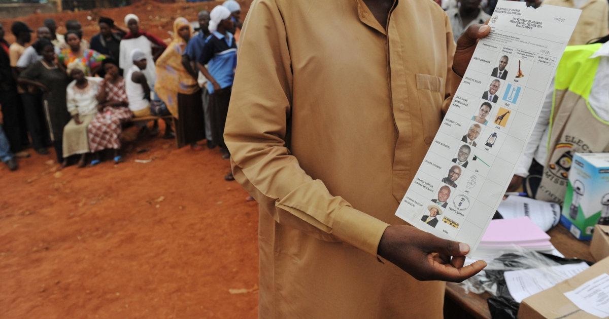 A voter in Uganda shows a blank ballot while waiting to vote.</p>