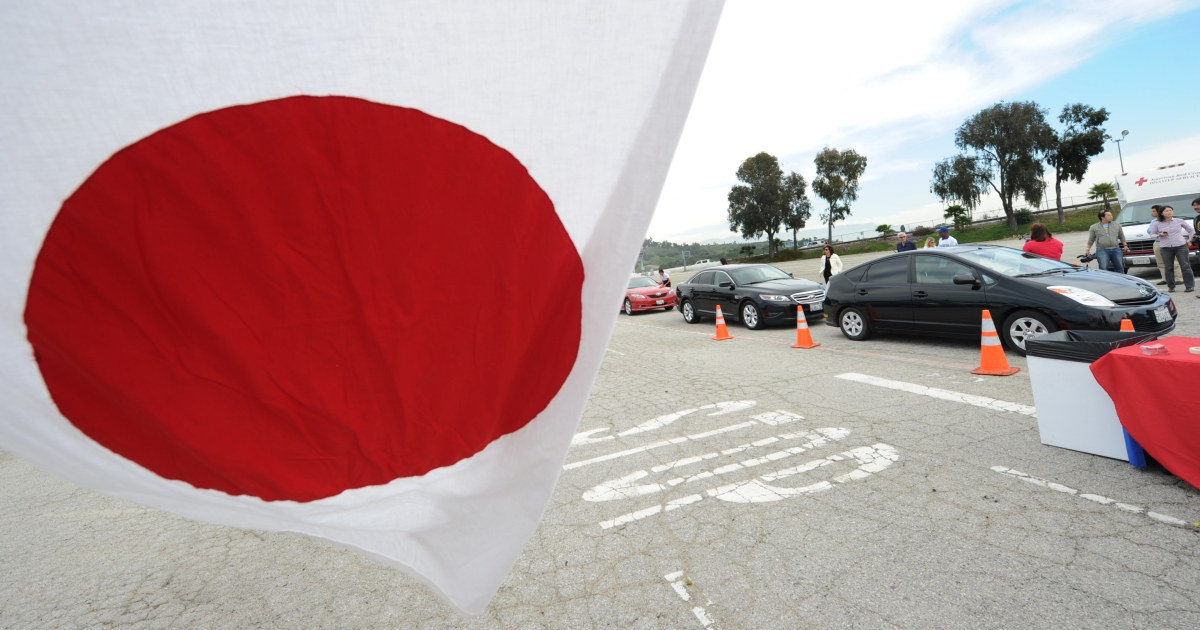 The Japanese flag flies as people make donations during a 'drive-through' fundraiser benefiting the American Red Cross Japan Tsunami Fund at the Dodger Stadium in Los Angeles on March 15, 2011.</p>