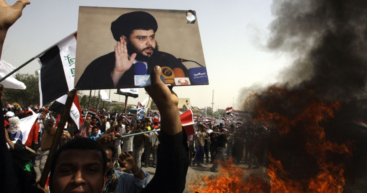 A supporter of Iraqi Shiite radical leader Moqtada al-Sadr shouts slogans while holding his picture near burning US flags in Baghdad on April 9, 2011. Sadr freed a former US soldier today on