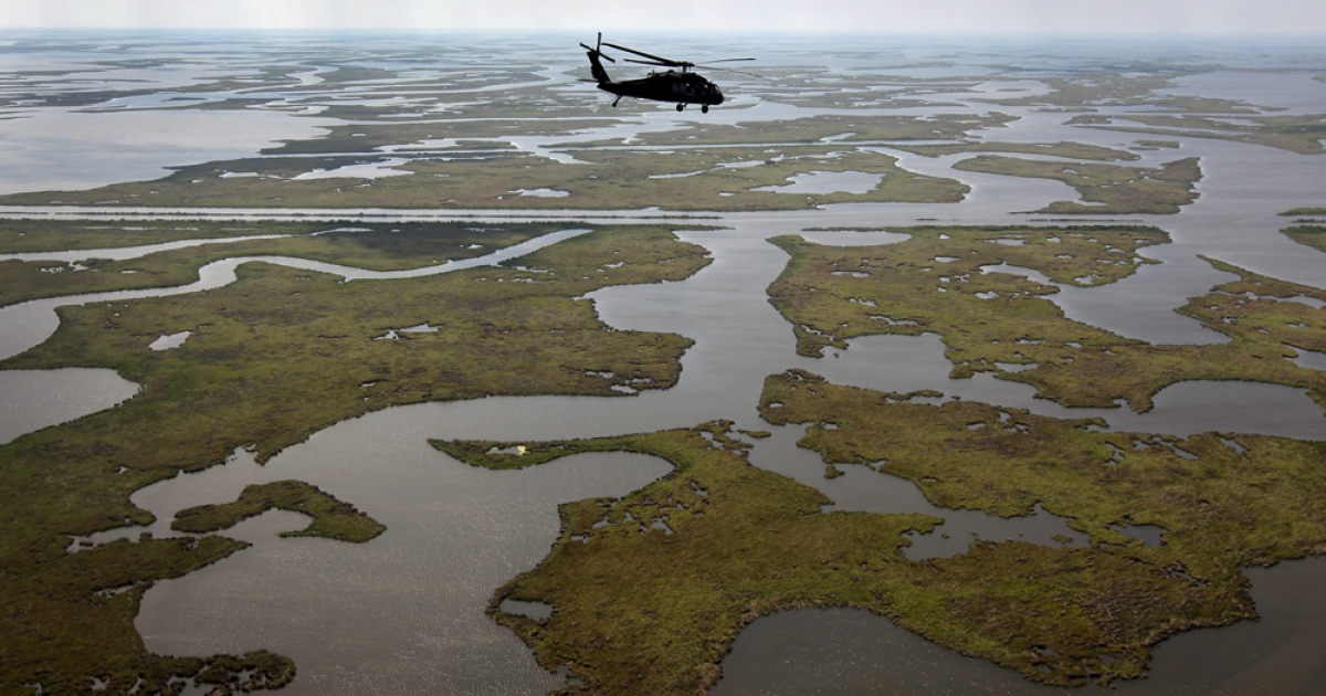 A Louisiana National Guard blackhawk flies over marshland on April 19, 2011 in route to Middle Ground in southern Louisiana. The 2010 BP oil spill coated Gulf coast marshes and beaches.</p>