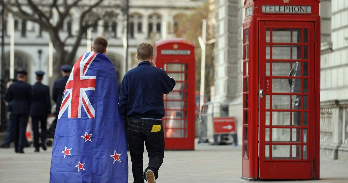 Two young men leave, one wearing a New Zealand flag — which looks almost exactly like the Australian flag —after a service of remembrance at the Cenotaph on Whitehall on April 25, 2011 in London, England.</p>