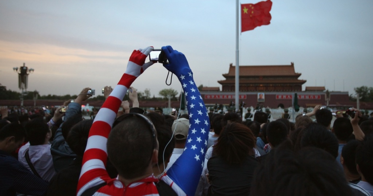 An American man watches the customary ceremony of lowering flag at Tiananmen Square on May 11, 2011 in Beijing, China.</p>