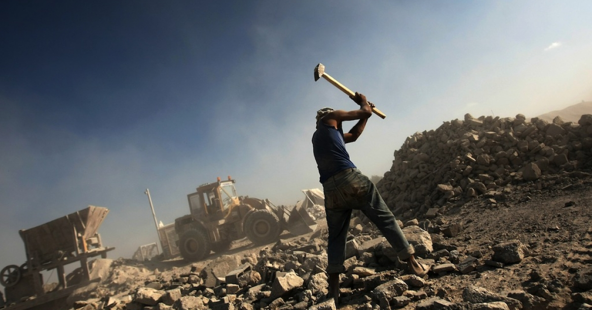 A Palestinian laborer works at a factory recycling the ruins of houses in order to use them in new construction sites in Gaza City on June 1, 2011.</p>