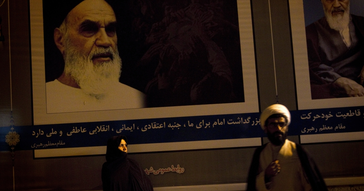 An Iranian clergyman walks past a veiled woman standing under the portraits of Iran's late founder of Islamic Republic, Ayatollah Ruhollah Khomeini on June 3, 2011.</p>