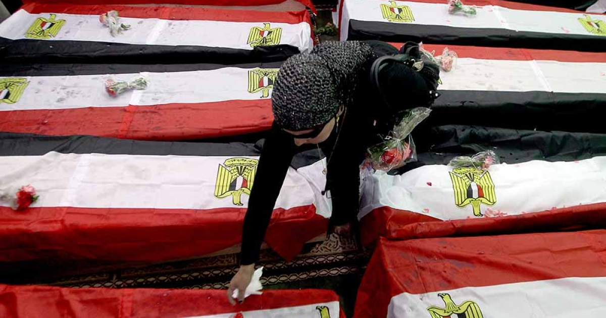 An Egyptian woman lays flowers on the flag-draped coffins of 19 unidentified victims of Tahrir Square.</p>