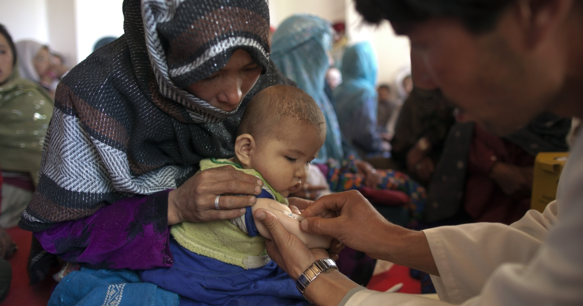 Vaccinator gives a measles shot to a baby at a mobile health clinic in the mountain village of Raquol, in Panjab district, Afghanistan.</p>