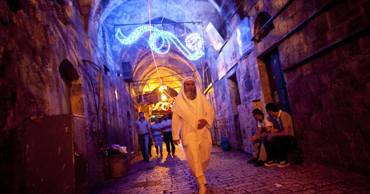 A Palestinian man walks towards the Damascus gate during the Jerusalem Festival of Lights on June 15, 2011 at Jerusalem's Old City, Israel. The festival opened on Wednesday night and will run for a week in the Old City of Jerusalem, hosting Israeli and international artists and creators who will display their installations throughout the week.</p>