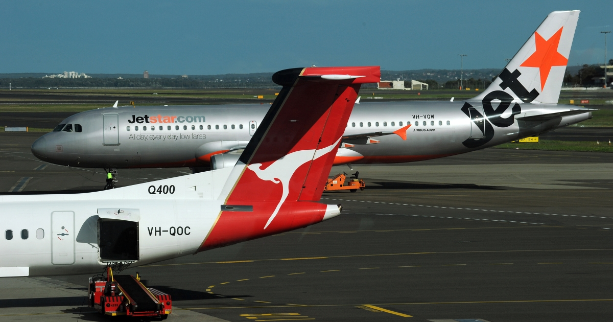 A Jetstar plane (top) is seen taxiing past a Qantas plane (below) on the tarmac at the domestic airport in Sydney on June 21, 2011.</p>